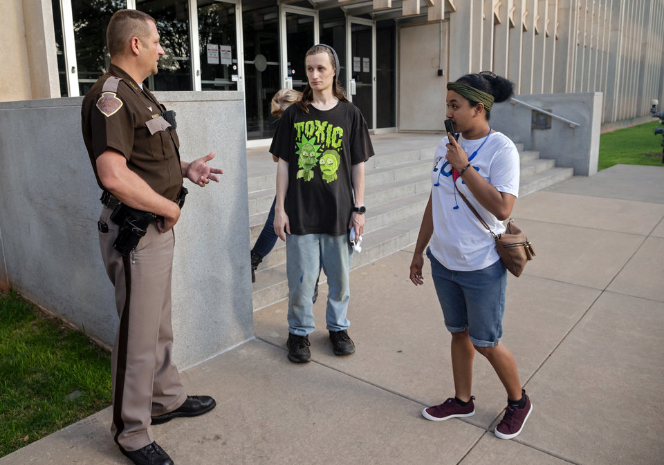 Photo - A Oklahoma Highway Patrol trooper talks to people that were not able to make it inside the Oklahoma Employment Securities Commission (OESC) to try and resolve issues that have prevented them from receiving unemployment payments on Friday, June 26, 2020, in Oklahoma City, Okla.   [Chris Landsberger/The Oklahoman]