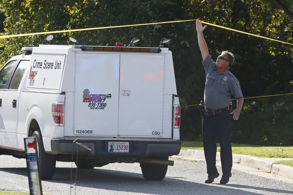 Photo -  A police officer stretches to raise crime scene tape for a crime scene unit to pass under at the scene where a shooting suspect was fatally shot during a police chase in Monday, Sept. 9, 2019, in northwest Oklahoma City. [AP Photo/Sue Ogrocki]