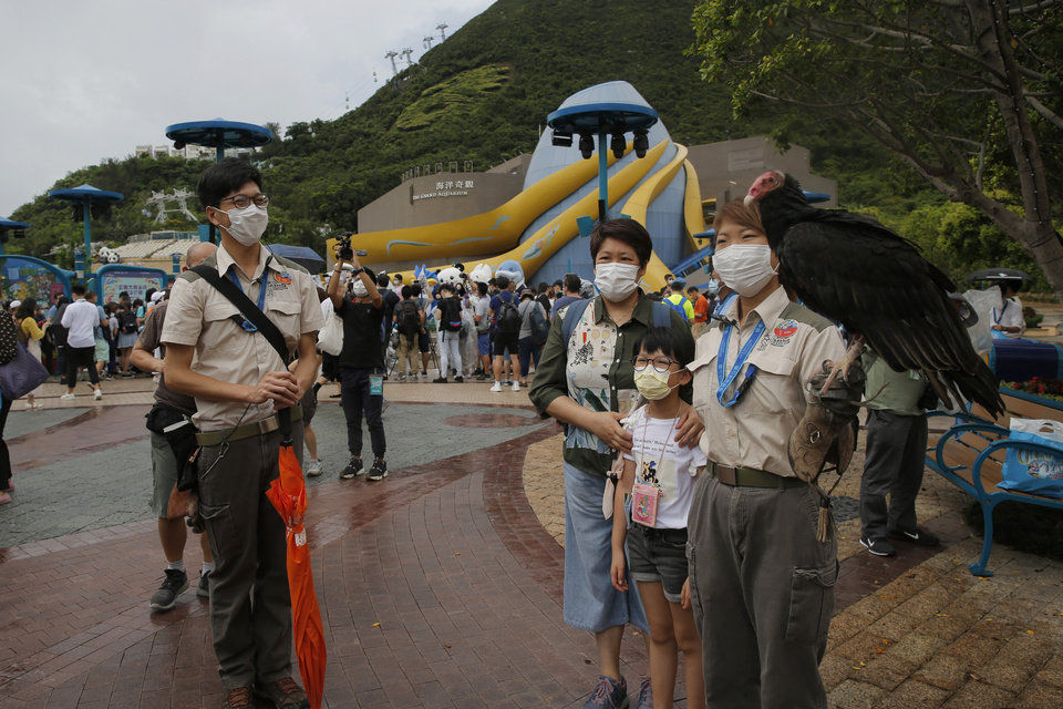 Photo -  Guests wearing face masks to prevent the spread of the new coronavirus, pose for a photograph at Ocean Park in Hong Kong, Saturday, June 13, 2020. Hong Kong Ocean Park reopened Saturday after nearly four months of closure due to the coronavirus pandemic. The animal and nature-themed attraction combines pandas, penguins, roller coasters and other rides, and has been a Hong Kong icon since its opening in 1977. (AP Photo/Kin Cheung)