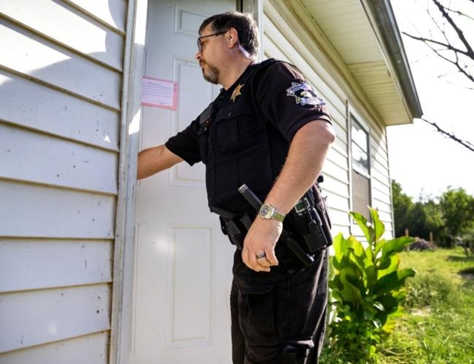 Photo -  Oklahoma County Sheriff's Deputy Brett Price, of the Field Services Bureau-Civil Division, enters a rental house to make sure it is cleared out as he serves a lock out notice in 2019.   [Chris Landsberger/The Oklahoman Archives]