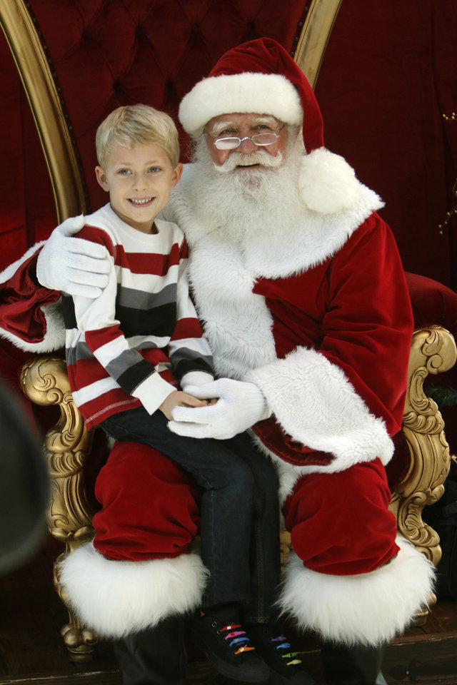Photo -  Isaih Jourdan-Muhn, then 7, has his photo taken with Santa in 2014 in the Devon Energy Center during Downtown in December in Oklahoma City. [Photo by Paul Hellstern, The Oklahoman Archives]