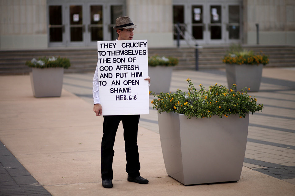 Photo - Caleb Hickam, of Amarillo Texas, protests a Black Mass at the Civic Center Music Hall, Sunday, Sept. 21, 2014.  Photo by Garett Fisbeck, For The Oklahoman