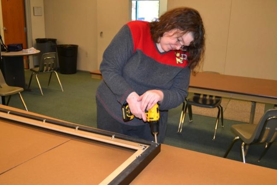 Photo -  Julie, a client at the Dale Rogers Training Center, works on the frame that was built to preserve a replica of the original Oklahoma flag that now hangs at the Oklahoma History Center. [PHOTO PROVIDED]
