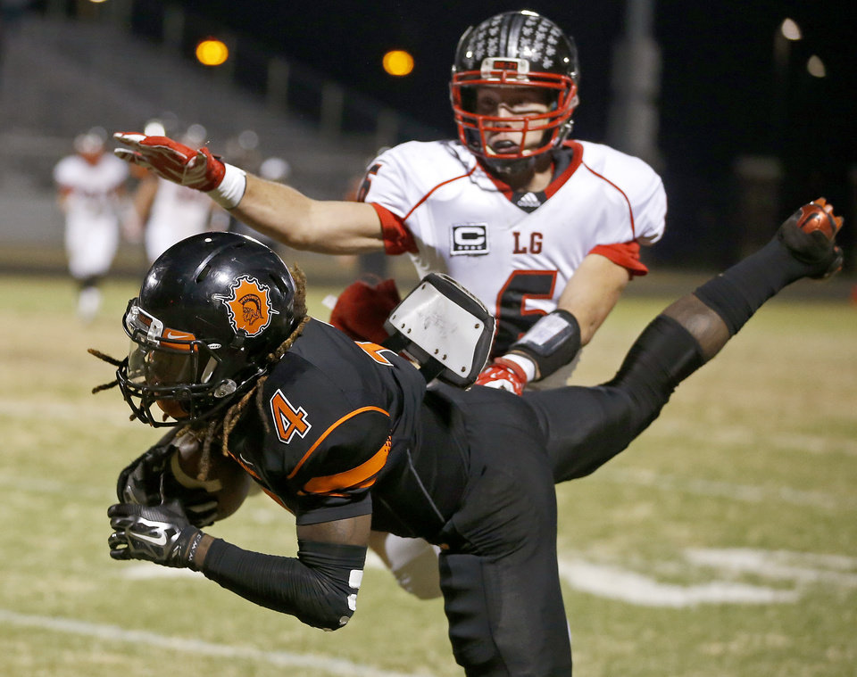 Photo - Dameko Doddles makes a reception in front of Locust Grove's Jason Pirtle during their high school football playoff game at Douglass in Oklahoma City, Friday, Nov. 28, 2014. Photo by Bryan Terry, The Oklahoman