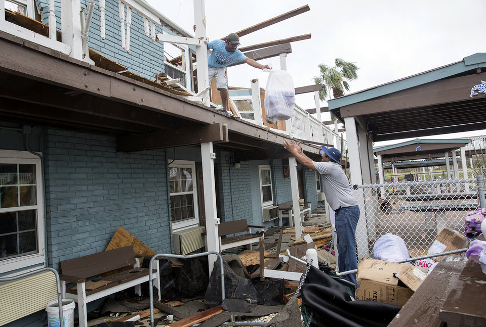 Photo - Neal Bhakta, 40, tosses a bag of personal belongings to his cousin, Vishal Bhakta, 36,  in Rockport, Texas, Sunday, Aug. 27, 2017. Hurricane Harvey destroyed the Surfside Inn Suites owned by Neal Bhakta. (The Victoria Advocate via AP)