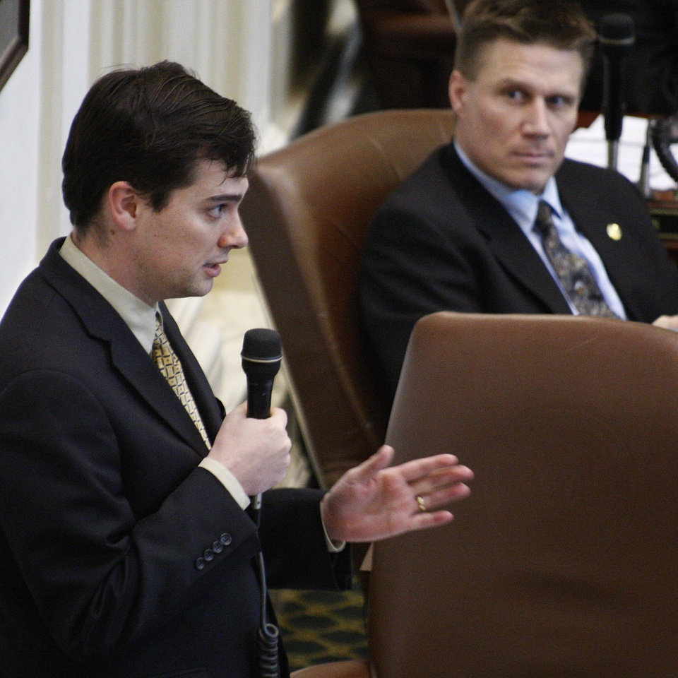 Photo - Oklahoma state Rep. Jason Murphey R-Guthrie, speaks on the floor of the Oklahoma House in Oklahoma City, Thursday, March 13, 2008, as state Rep. Todd Thompson, R-Ada, looks on at right. (AP Photo) ORG XMIT: OKSO106