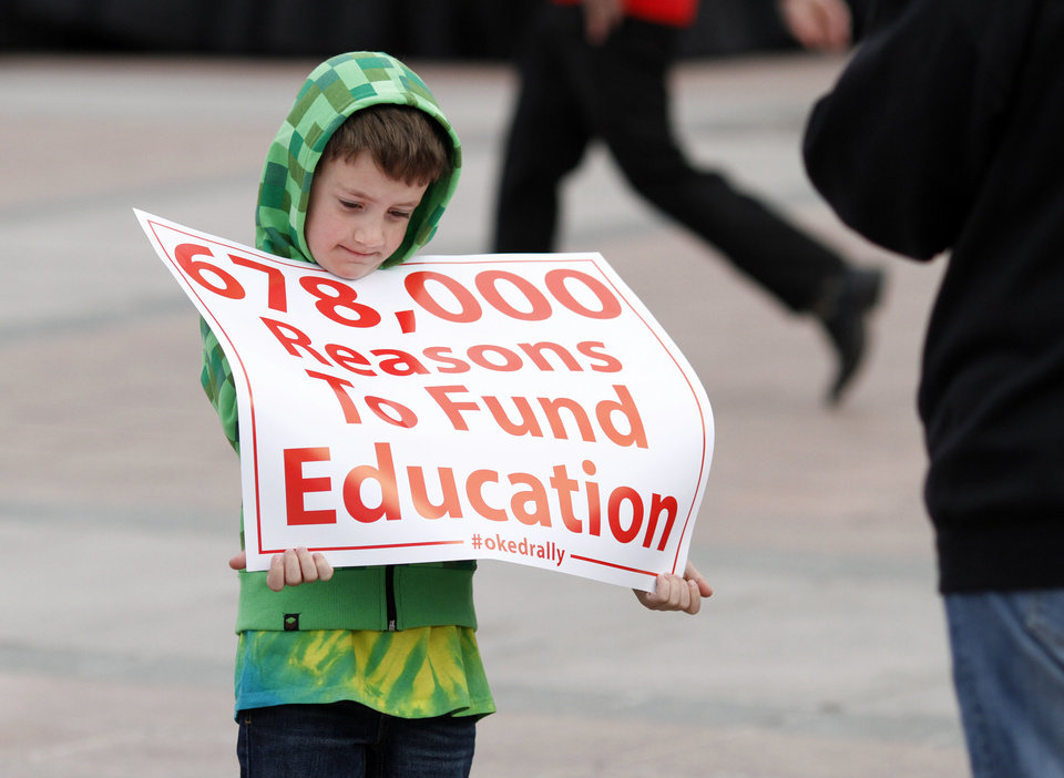 Photo - Gregson Sloan, a Mustang Public School student holds a sign as he participates during a rally to appeal to lawmakers to make education funding a priority at the state capitol in Oklahoma City, Okla. on Monday, March 31, 2014. Educators, parents and community members from across Oklahoma gathered at the statehouse to make their voices heard by lawmakers. Photo by K.T. King, The Oklahoman