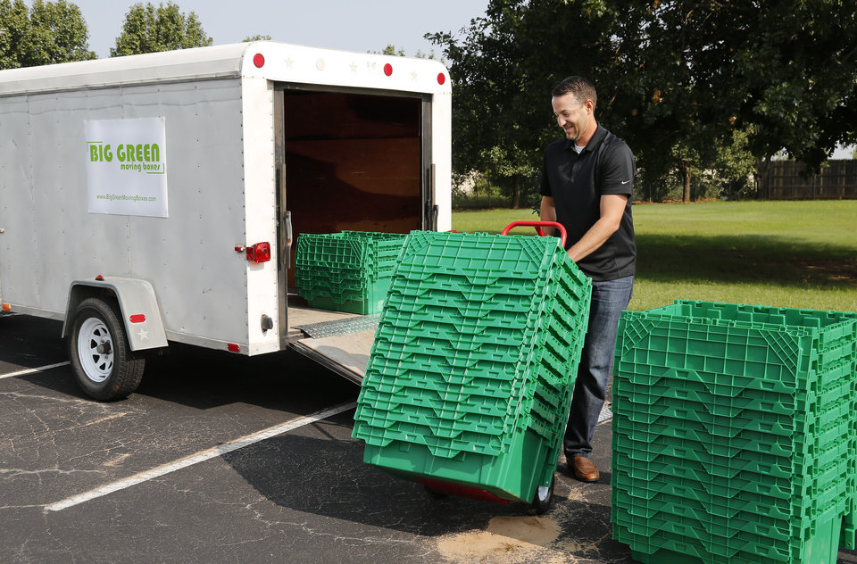 Photo -  Steven Embree unloads moving boxes from a trailer Tuesday.