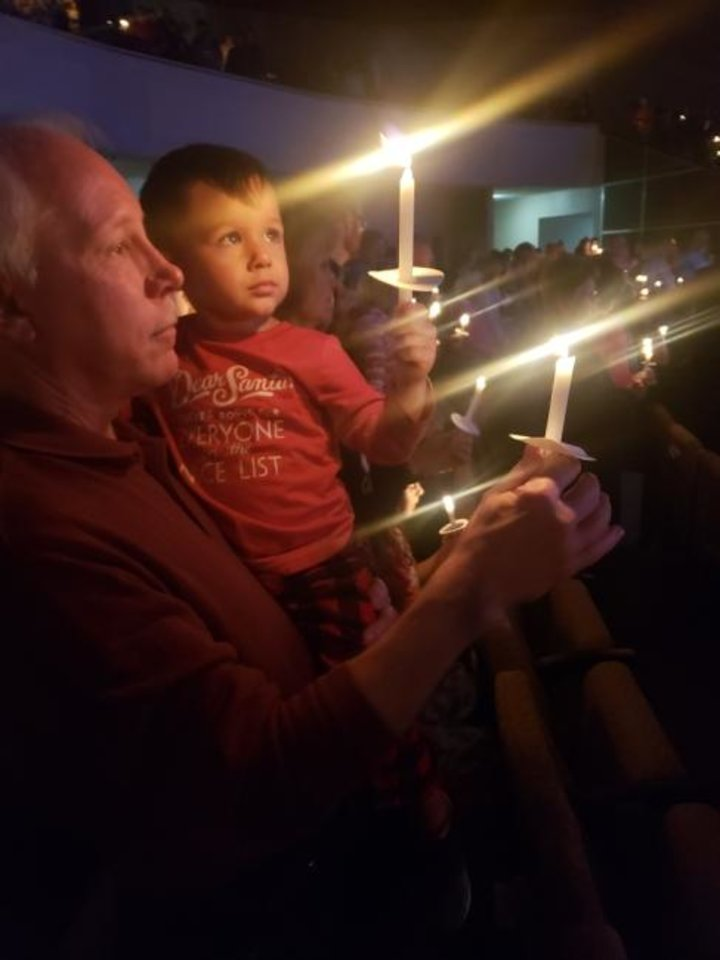 Photo -  Max Lonsdale holds Ryker Perales as they both hold lighted candles during a  Candlelight Service held on Christmas Eve in a previous year at Council Road Baptist Church in Bethany. [Photo provided]