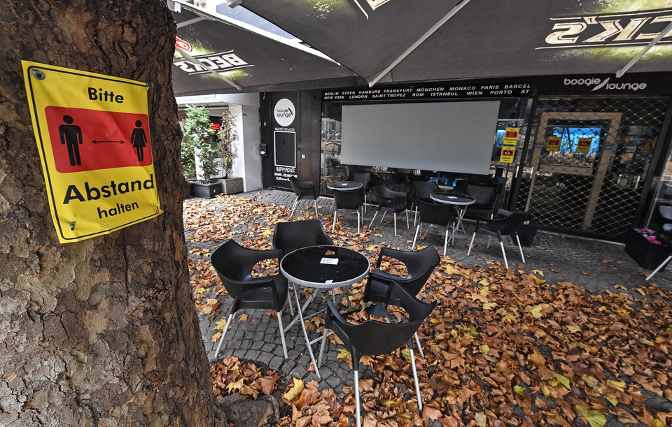 Photo -  A sign reads 'Please keep distance' in front of a closed bar Monday in the city center of Essen, Germany. A month-long partial lockdown due to the coronavirus pandemic becomes effective in Germany on Monday. [Martin Meissner/The Associated Press]