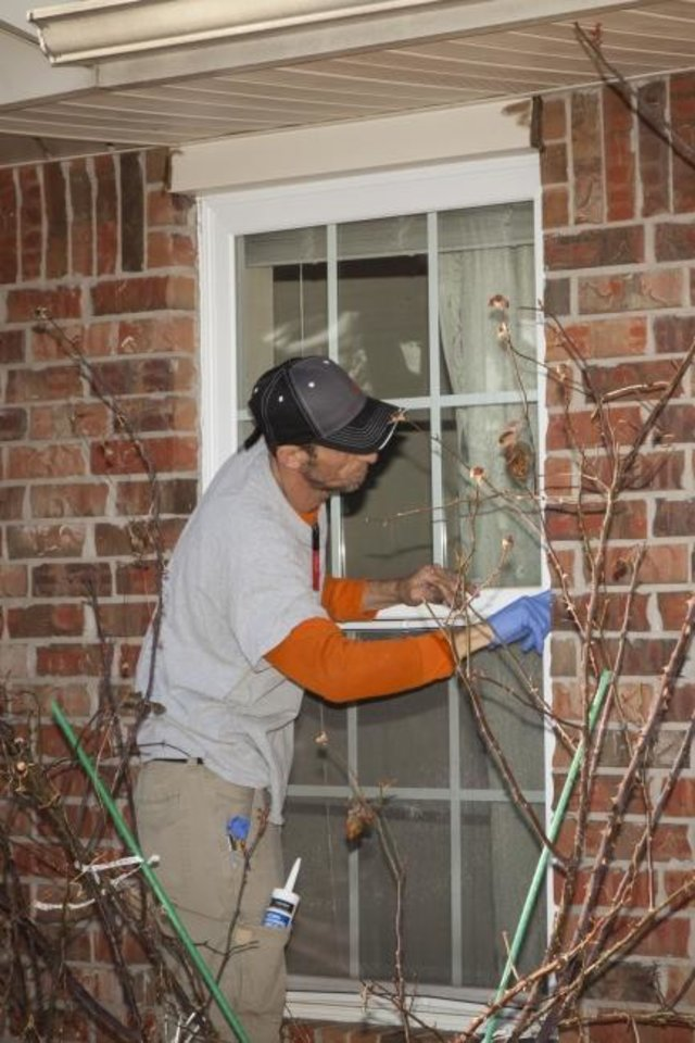Photo -  A Skyline Energy Solutions employee caulks a window at the Mount Olive Senior Cottages development in northeast Oklahoma City on Monday. The company worked with Oklahoma Gas and Electric Co. to make energy upgrades at the development, which provides affordable housing for low- and moderate-income seniors.