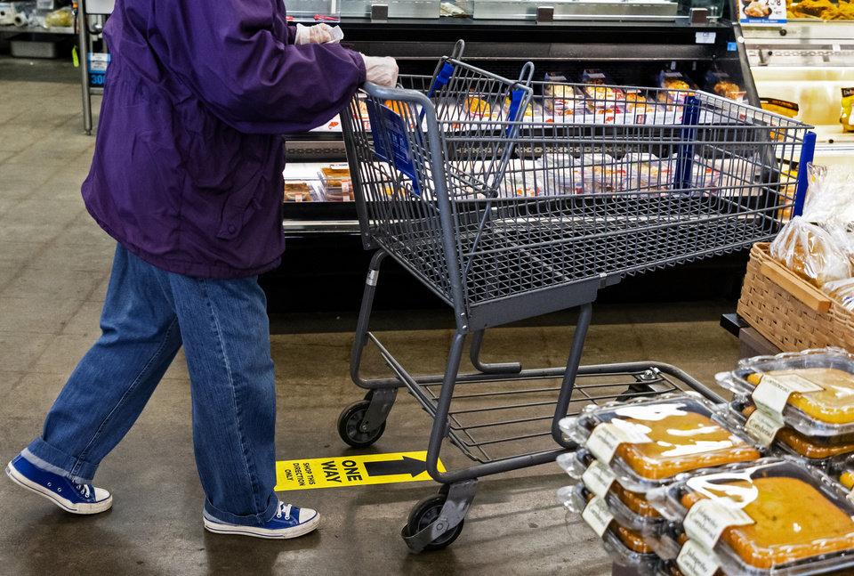 Photo - Arrows on the ground mark the direction of shopping for each aisle as customers push their cart through the Homeland located at 1108 NW 18th St. in Oklahoma City, Okla. on Monday, April 13, 2020. The store has taken extra steps to help protect its employees and customers during the coronavirus pandemic.   [Chris Landsberger/The Oklahoman]