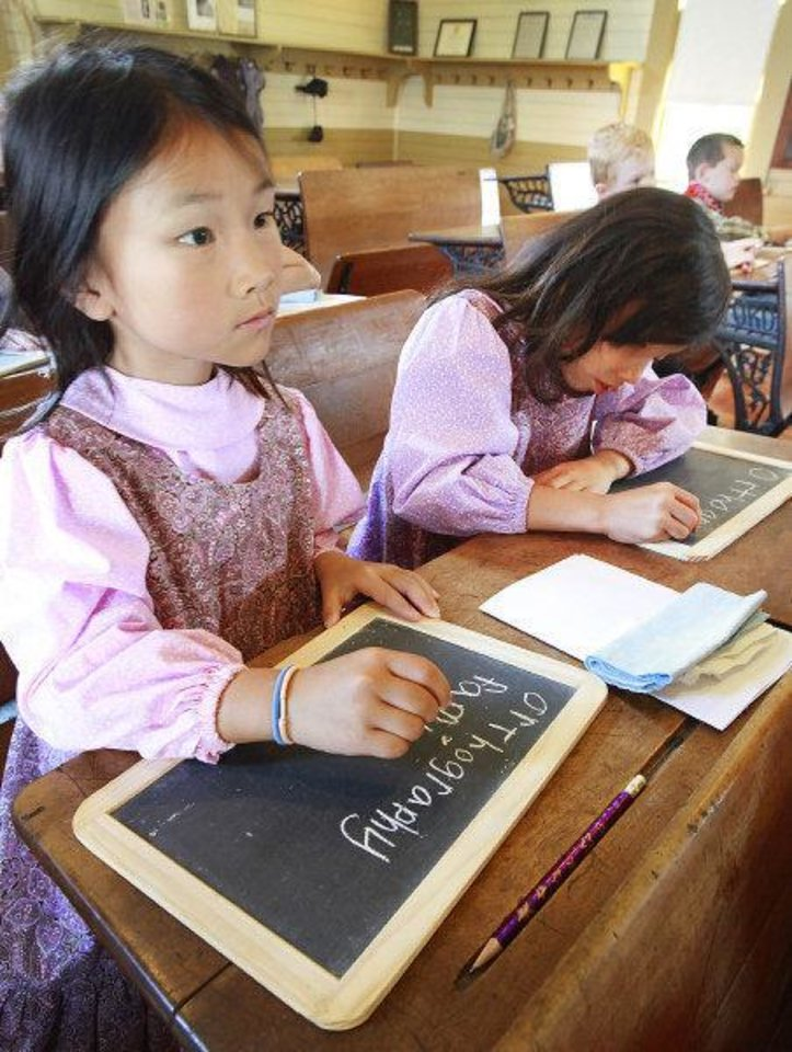 Photo - Joy Hampton, 7, left, and her sister Hope, 7, copy a writing lessen on their slates Wednesday during 1889 Summer Camp at Edmond's historic school house. PHOTO BY DAVID MCDANIEL, THE OKLAHOMAN  David McDaniel