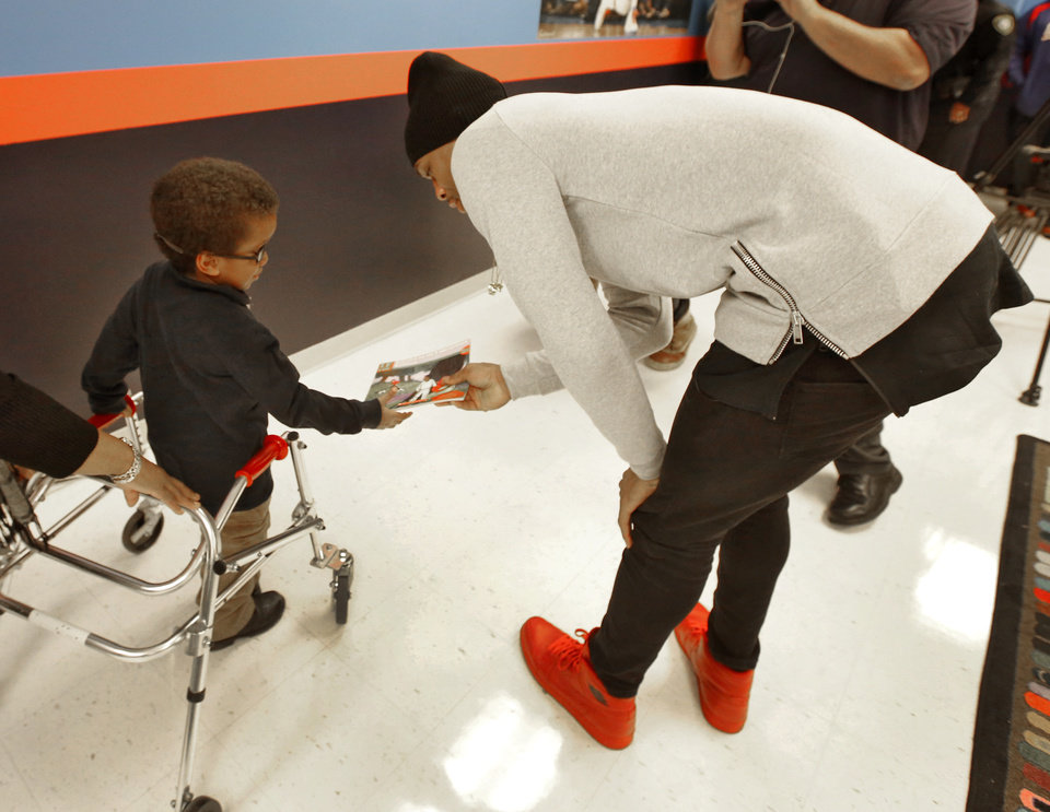Photo - Oklahoma City Thunder's Russell Westbrook gives a book to Carlos Watts, kindergarten student at Martin Luther King Elementary School during the opening of Russell's Reading Room in Oklahoma City, Monday February, 23 2015. Westbrook joined students and educators for the dedication of the new center. Photo By Steve Gooch, The Oklahoman