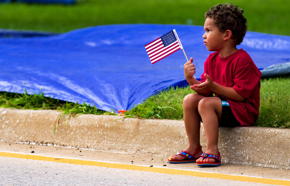 Photo - Levi Gilkey, 3, waves his American Flag as we waits for the start of the Bethany Freedom Festival parade in Bethany, Okla. on Thursday, July 4, 2019.    [Chris Landsberger/The Oklahoman]