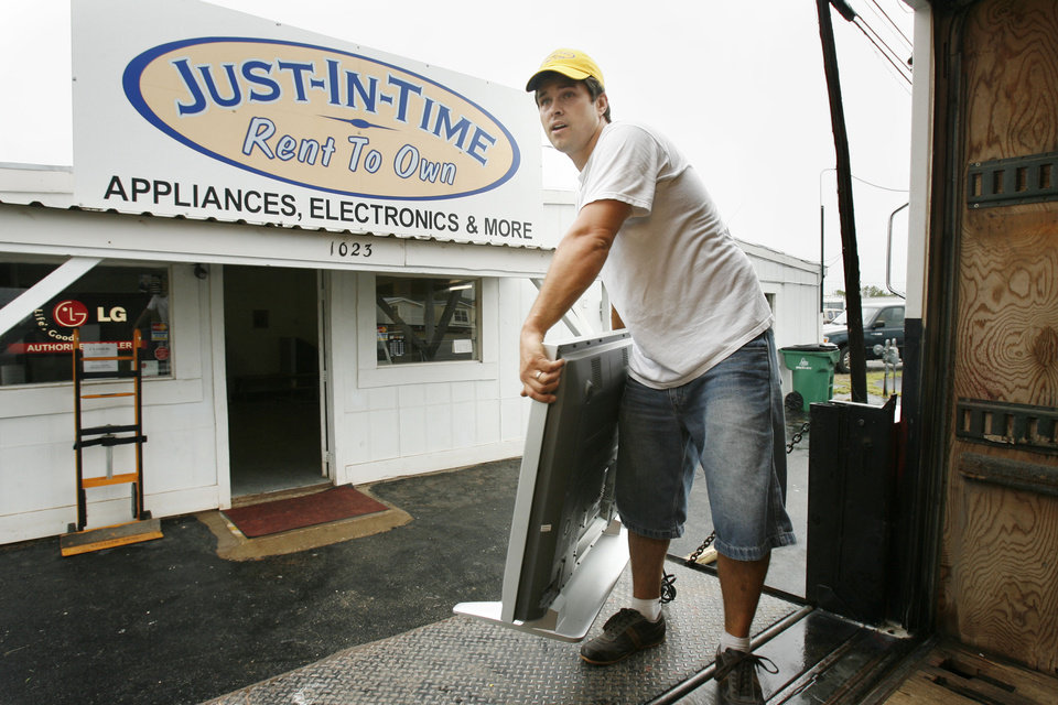 Photo - Alerted to a rising creek by officials, Justin Nimmo moves rental items from his Just in Time rental store to a truck in Purcell, Oklahoma on Sunday morning, August 19, 2007.   His store was flooded by the same creek earlier this year.  BY STEVE SISNEY, THE OKLAHOMAN