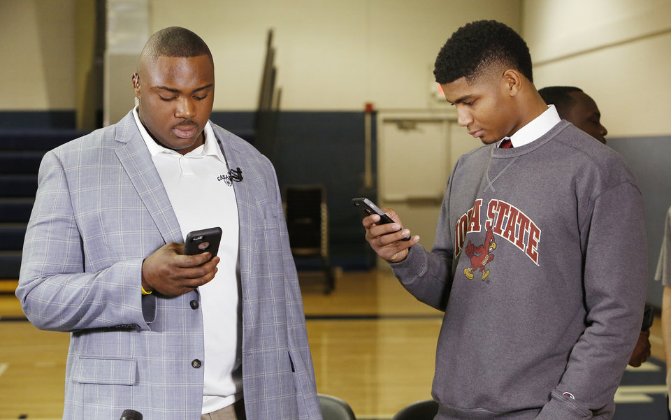 Photo - Casady High School football athletes Josh Wariboko-Alali and Denver Johnson texting on their phones during signing day ceremonies at Casady High School in Oklahoma City Wednesday, Feb. 4, 2015. Photo by Paul B. Southerland, The Oklahoman