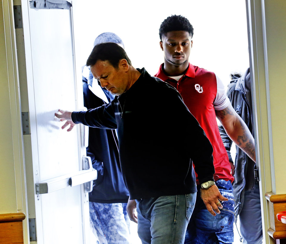 Photo - University of Oklahoma Sooners (OU) Running Back Joe Mixon walks to the conference room as head coach Bob Stoops holds the door for a press conference in Norman, Okla., on Friday, Dec. 23, 2016.  Mixon spoke for the first time since the release of a 2014 video showing him striking Amelia Molitor. Photo by Steve Sisney, The Oklahoman