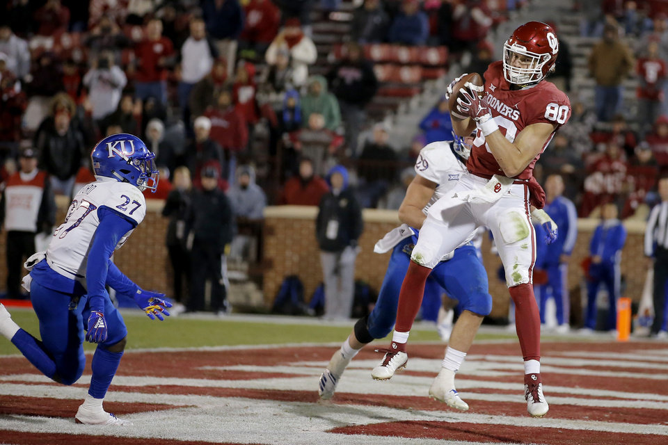 Photo - Oklahoma's Grant Calcaterra (80) catches a touchdown pass beside Kansas' DeAnte Ford (27) during a college football game between the University of Oklahoma Sooners (OU) and the Kansas Jayhawks (KU) at Gaylord Family-Oklahoma Memorial Stadium in Norman, Okla., Saturday, Nov. 17, 2018. Photo by Bryan Terry, The Oklahoman
