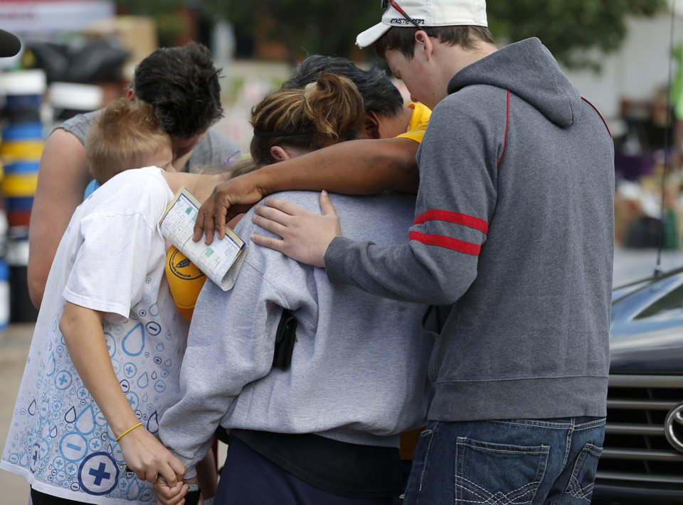 Photo - Residents pray outside the entrance to the Plaza Towers addition in Moore on Wednesday, May 22, 2013. A tornado damage the area on Monday, May 20, 2013. Photo by Bryan Terry, The Oklahoman