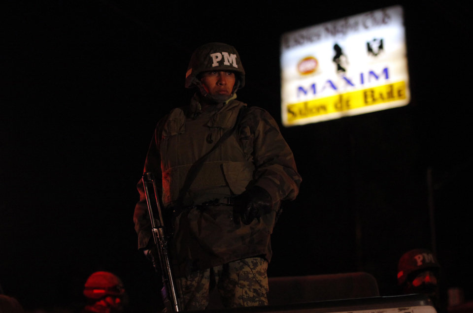 Photo - DRUG WAR / VIOLENCE:	**ADVANCE FOR MONDAY, DEC. 7** In this Nov. 19, 2009 photo, soldiers stand guard at a crime scene where two women and a man were killed by gunmen at a bar in Ciudad Juarez, Mexico. Violent death is a part of life in Ciudad Juarez, a city on the banks of the Rio Grande, with 2,250 killings this year, a rate of 173 per 100,000 residents. (AP Photo/Guillermo Arias) ORG XMIT: MXGA304