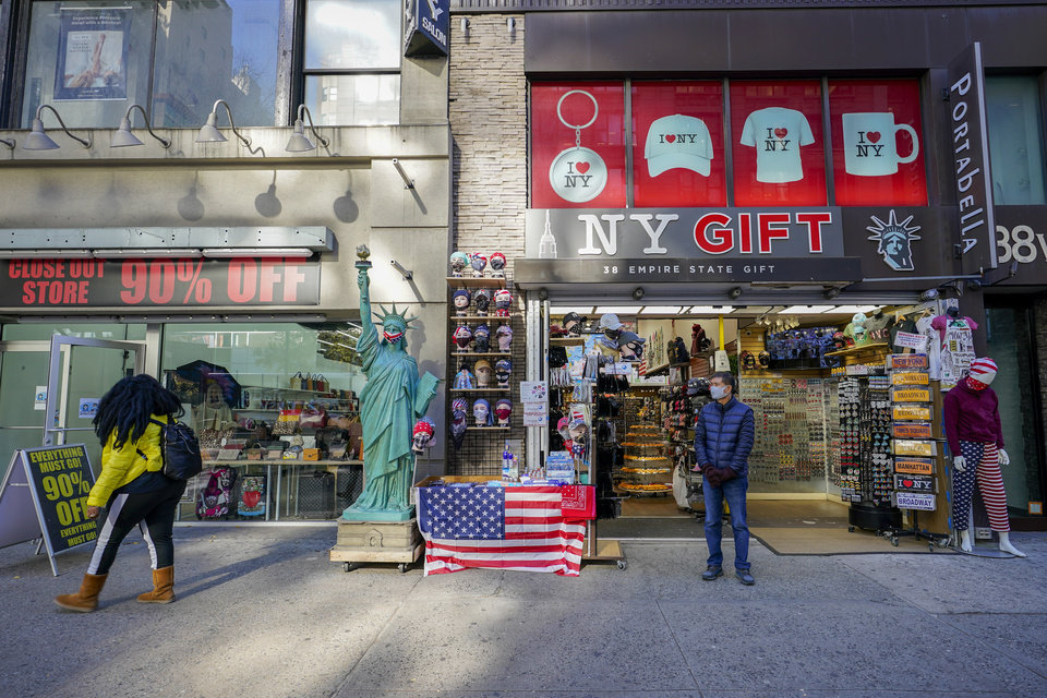 Photo -  A shop keeper at a gift shop along 34th Street stands on the sidewalk waiting for customers Friday in New York. [Mary Altaffer/The Associated Press]