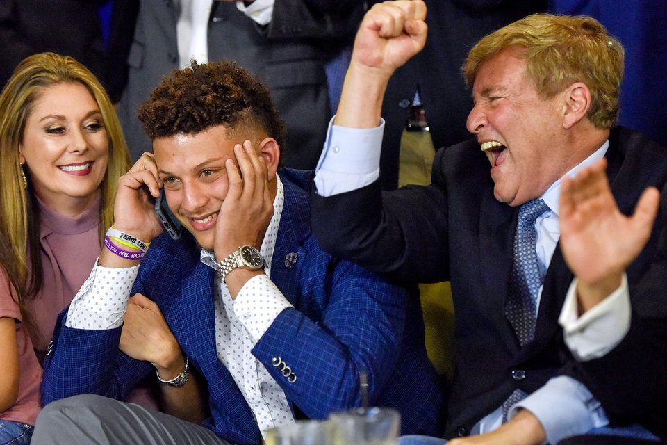 Photo -  Patrick Mahomes, center, and Leigh Steinberg, right, react while Mahomes is on a call with the Kansas City Chief, during an NFL Draft watch party in April 2017. Mahomes was the Chiefs' No. 1 draft choice. [Chelsea Purgahn/Tyler Morning Telegraph via AP, File]