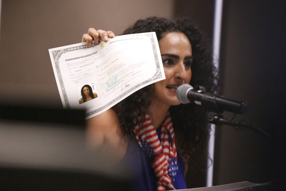 Photo -  Sara Bana holds up her documentation paperwork as she addresses the trust members. Bana called on the sheriff's office and the trust to cut all ties with ICE. [Paxson Haws/The Oklahoman]