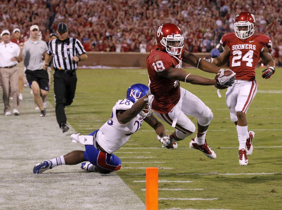 Photo - OU's Justin Brown (19) dives past KU's Marquis Jackson (28) foe a touchdown as OU's Brennan Clay (24) watches  during the college football game between the University of Oklahoma Sooners (OU) and the Kansas Jayhawks (KU) at Gaylord Family-Oklahoma Memorial Stadium in Norman, Okla., Saturday, Oct. 20, 2012. Photo by Bryan Terry, The Oklahoman