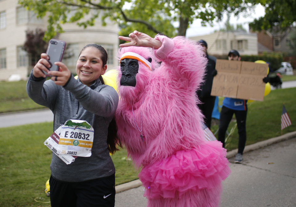 Photo - Cassie Tisho takes a selfie with Susan Phillips dressed as a gorilla on Gorilla Hill during the 2017 Oklahoma City Memorial Marathon Sunday, April 30, 2017.  Photo by Sarah Phipps, The Oklahoman