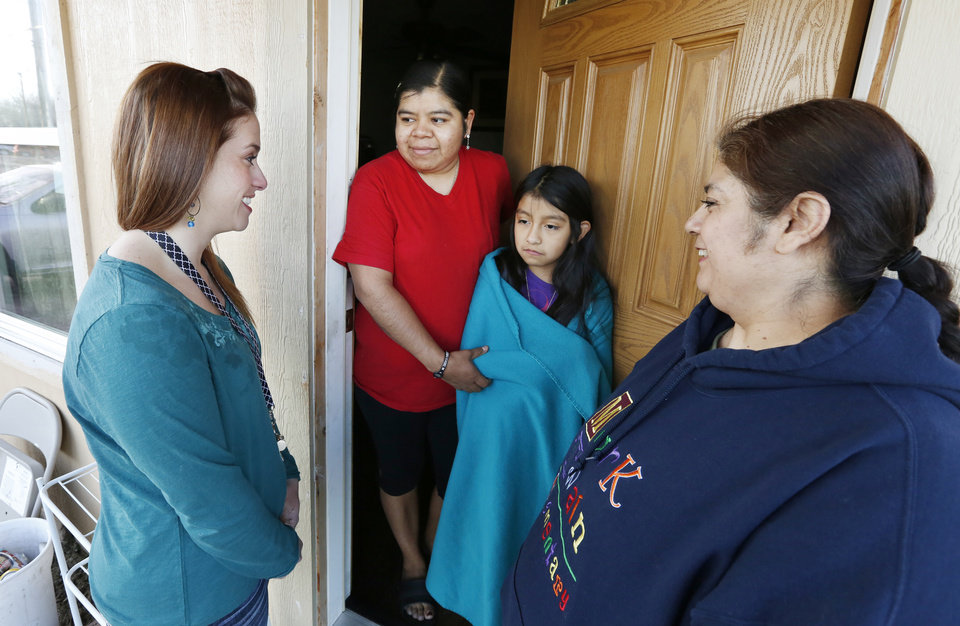 Photo -  Mark Twain Elementary School kindergarten teacher Kristen Widener, left, and school district bilingual assistant Toni Ramirez, at right, visit Friday with Patricia Rosales and her daughter, Erica, a third-grader, in the Westlawn neighborhood in Oklahoma City. Photo by Paul B. Southerland, The Oklahoman   PAUL B. SOUTHERLAND -  PAUL B. SOUTHERLAND