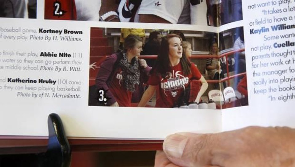 Photo - Duncan Schools interim superintendent Glenda Cobb shows a photo of Katherine Hruby as a member of the high school's volleyball team in a recent yearbook. Photo by Jim Beckel.