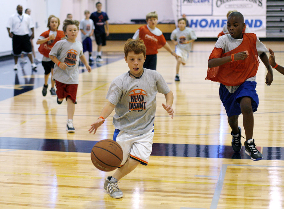 Photo - Ethan Boyer, 10 of Oklahoma City, drives the basketball down the court during the second day of the Kevin Durant basketball camp at Heritage Hall in Oklahoma City, Thursday, June 30, 2011.  Photo by Garett Fisbeck, The Oklahoman