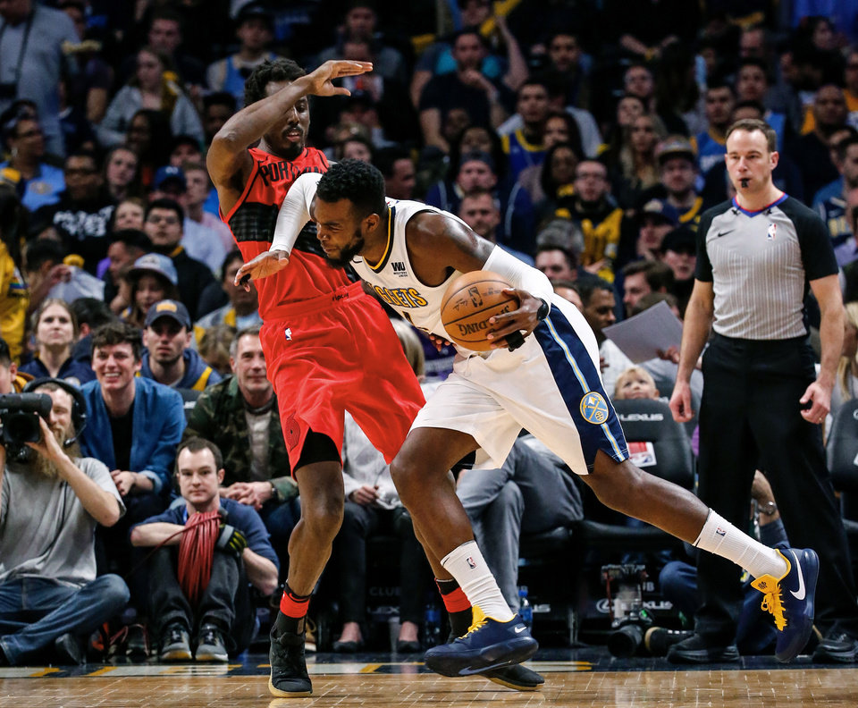 Photo - Denver Nuggets forward Paul Millsap (4) collides with Portland Trail Blazers forward Al-Farouq Aminu (8) during the third quarter of an NBA basketball game, Monday, April 9, 2018, in Denver. Denver won 88-82. (AP Photo/Jack Dempsey)