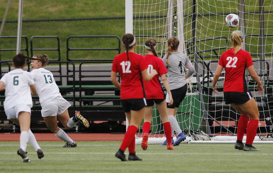 Photo - NN #13 Jamie McGinnis, left, scores against M#1Ashlee Jackson in the first half during the 6A girls state soccer championship between Norman North Timberwolves and Mustang Bronchos at Taft Stadium in Oklahoma City, Saturday, May 11, 2019.  [Doug Hoke/The Oklahoman]