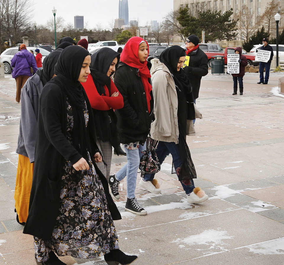 Photo - Two protestors, seen at far right, were at the state Capitol when Muslims walked across the south plaza to enter the building to be part of the day's events. More than 100 participated in Muslim Day at the Capitol on Monday, March 4, 2019.  The annual event is sponsored by the Council on American-Islamic Relations-Oklahoma chapter. Interfaith supporters   held signs welcoming Muslim guests as they arrived at the Capitol. A man and a woman stood nearby, displaying placards expressing concerns about crimes committed by some Muslims in the recent past.   Photo by Jim Beckel, The Oklahoman.