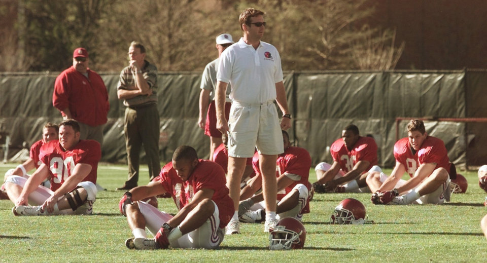 Photo - OU SPRING FOOTBALL PRACTICE: COACH BOB STOOPS STANDS NEAR DAMIAN MACKEY DURING WARM UPS.