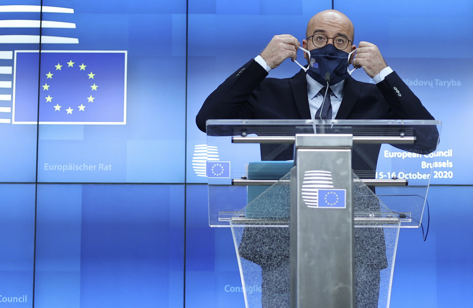 Photo -  European Council President Charles Michel puts on his protective face mask after speaking during a media conference at an EU summit in Brussels, Thursday, Oct. 15, 2020. European Union leaders met in person for the first day of a two-day summit, amid the worsening coronavirus pandemic, to discuss topics ranging from Brexit to climate and relations with Africa. (Kenzo Tribouillard, Pool via AP)