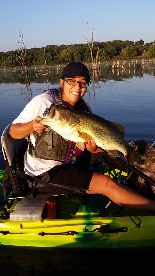 Photo -  Taylor Wilson of Bartlesville shows off a big bass that she caught while fishing from a kayak on Prague Lake. [PHOTO BY BRENT WILSON]