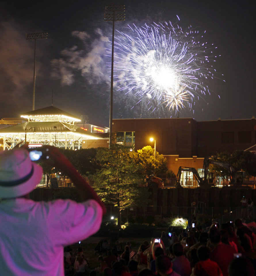 Photo - Hundreds of Oklahomans crammed into Bricktown to watch the Fourth of July fireworks over the Chickasaw Bricktown Ballpark on July 4, 2014 in downtown Oklahoma City.  Photo by KT King/The Oklahoman