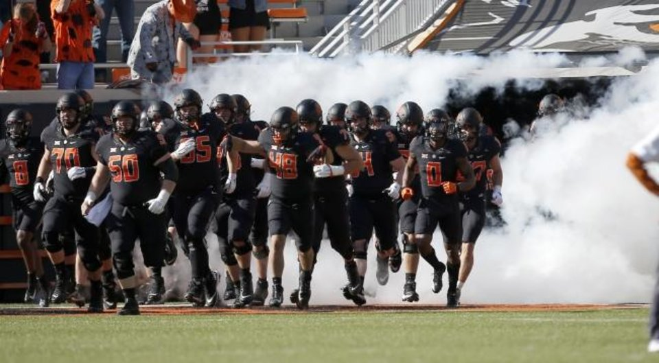 Photo -  Oklahoma State football players sport their black uniforms as they run on to the field ahead of a Halloween game against Texas. [Sarah Phipps,/The Oklahoman]