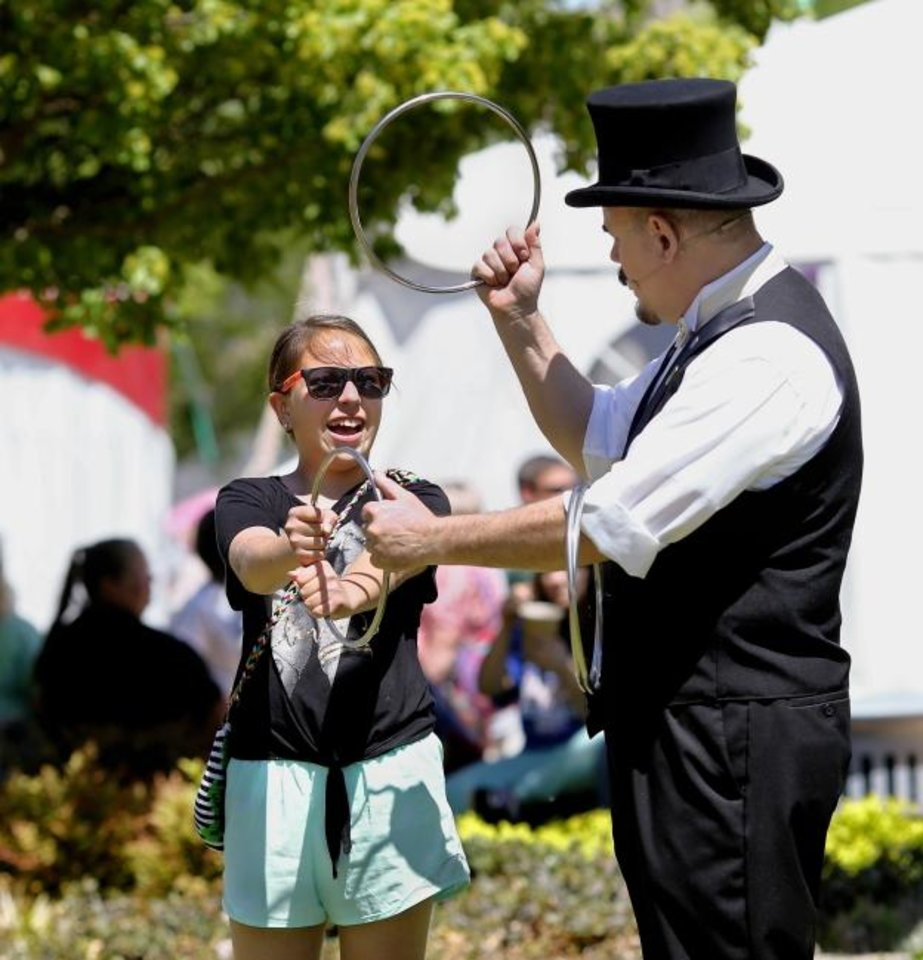 Photo -  Capstone the Magician works with audience volunteer Valentina Vergara, 10, of Norman, during his Chinese rings trick during Thursday's noon show. Capstone, who is based in Tulsa, is the official street performer at this year's Festival of the Arts. He is performing 40-minute sets at  at noon, 2:30 and 7:45 p.m. Friday and Saturday; and at noon, 2 and 4 p.m. Sunday.  Performances are on the Colcord Lawn at Bicentennial Park, near the Civic Center.   [Jim Beckel/The Oklahoman]