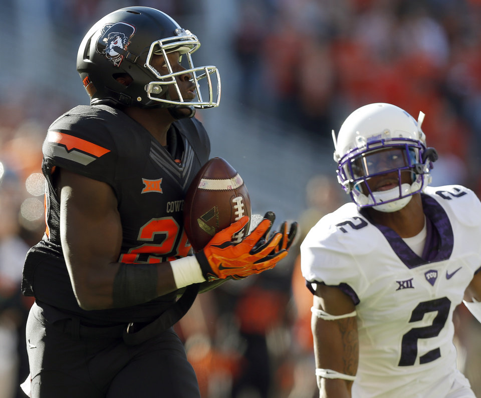 Photo - Oklahoma State's James Washington (28) makes a reception in front of TCU's Torrance Mosley (2) during the college football game between the Oklahoma State Cowboys (OSU) and TCU Horned Frogs at Boone Pickens Stadium in Stillwater, Okla., Saturday, Nov. 7, 2015. Photo by Sarah Phipps, The Oklahoman