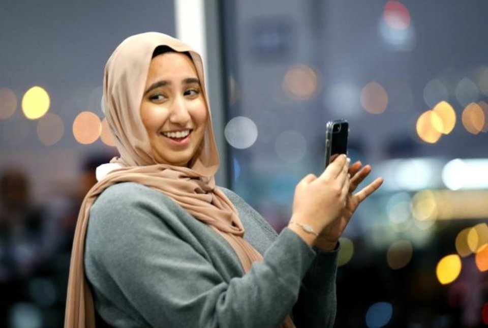 Photo -  Jenin Salus laughs before taking photos of friends during an evening celebrating