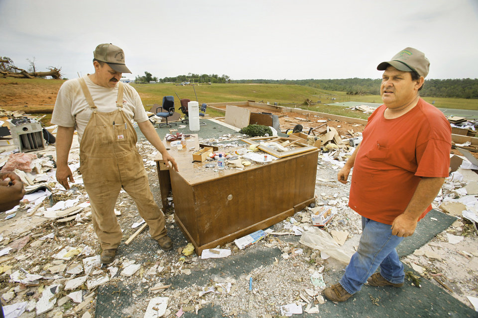 Photo - Cousins Glenn and Mike Rosenfelt marvel Wednesday at a desk that remained intact and in place at what was the administration building for Little Axe schools. The building and football stadium were blown away Monday by a tornado.