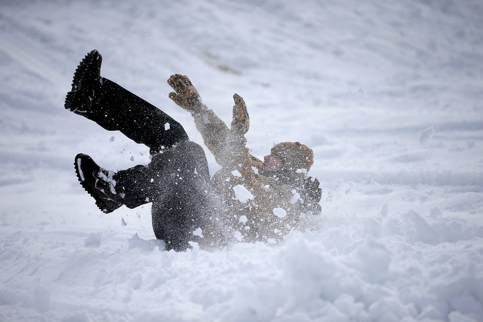 Photo - A person falls down while trying to sled down a hill along W Hefner Road in Oklahoma City after a winter storm dropped another layer of snow in Oklahoma City, Wednesday, Feb. 17, 2021. [Bryan Terry/The Oklahoman]