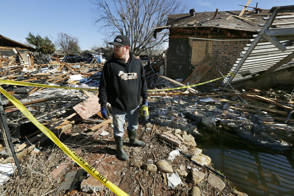 Photo -  Michael Boyd on Monday looks over the destruction of his grandparents' home at 12501 Whispering Hollow Drive. The damage happened Saturday during a massive explosion at their neighbor's home. [Photos by Paul Hellstern, The Oklahoman]
