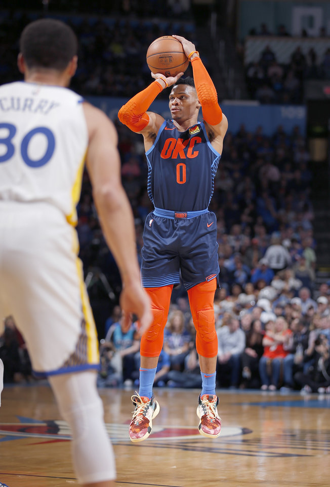 Photo - Oklahoma City's Russell Westbrook (0) shoots a basket in front of Golden State's Stephen Curry (30) during the NBA basketball game between the Oklahoma City Thunder and the Golden State Warriors at Chesapeake Energy Arena,  Saturday, March 16, 2019. Photo by Sarah Phipps, The Oklahoman