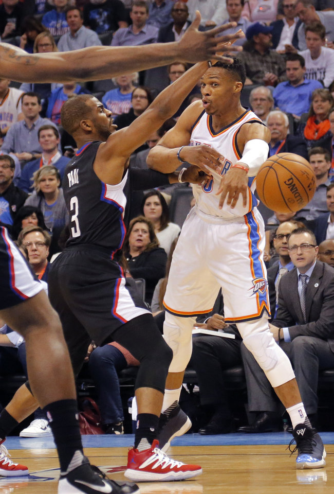 Photo - Oklahoma City's Russell Westbrook (0) passes the ball past Los Angeles Clippers' Chris Paul (3) during the NBA basketball game between the Oklahoma City Thunder and the Los Angeles Clippers at Chesapeake Energy Arena on Wednesday, March 9, 2016, in Oklahoma City, Okla. Photo by Chris Landsberger, The Oklahoman