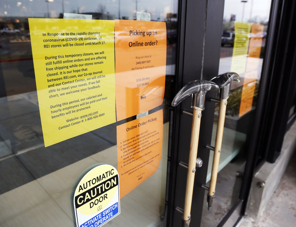 Photo - Signs on the door of the REI Co-op in Oklahoma City give information about its closure, Monday, March 16, 2020. REI has closed all of its retail stores until March 27 because of the coronavirus pandemic. [Nate Billings/The Oklahoman]